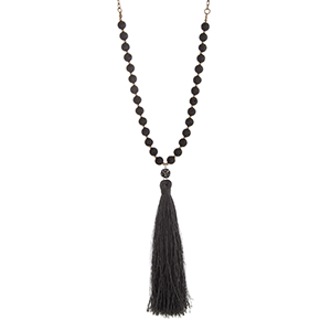 "Burnished gold tone necklace with black lava beads and a 5 1/4"" gray fabric tassel. Approximately 30"" in length."