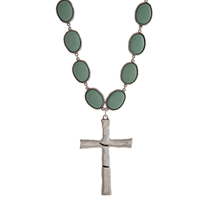 "Burnished silver tone necklace displaying mint green oval stone with a 3"" cross pendant. Approximately 23"" in length."