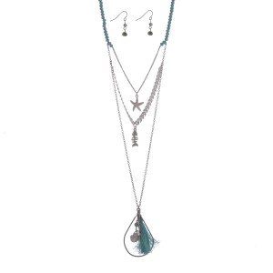 "Silver tone turquoise beaded layering necklace set displaying a chevron pattern with a starfish a fish charm and an open teardrop shape with a fabric tassel and sea life charms. Approximately 31"" in length."