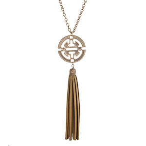 "Worn gold tone necklace displaying an Aztec inspired pendant with a gold faux leather 4"" tassel. Approximately 29"" in length."