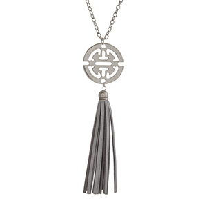 "Worn silver tone necklace displaying an Aztec inspired pendant with a silver faux leather 4"" tassel. Approximately 29"" in length."