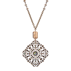 """Gold tone necklace with a filigree pendant and iridescent rhinestone accents. Approximately 32"""" in length."""