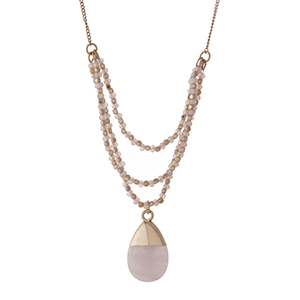 "Gold tone necklace with pale pink beads and a rose quartz natural stone pendant. Approximately 30"" in length."