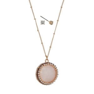 "Gold tone necklace with a rose quartz pendant accented with pave rhinestones. Approximately 24"" in length."