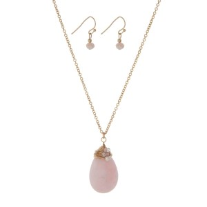 "Gold tone necklace set with a pale pink wire wrapped natural stone teardrop pendant and matching earrings. Approximately 24"" in length."