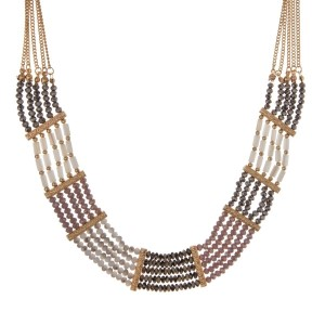 "Gold tone statement necklace with purple, gray, ivory and Dalmatian beads. Approximately 18"" in length."