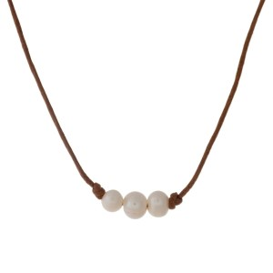 "Tan waxed cord necklace with three cream freshwater pearl beads. Approximately 16"" in length."