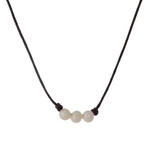 "Brown waxed cord necklace with three cream freshwater pearl beads. Approximately 16"" in length."