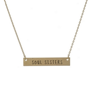 """Dainty gold tone necklace with a bar focal, stamped with """"Soul Sisters."""" Approximately 16"""" in length."""