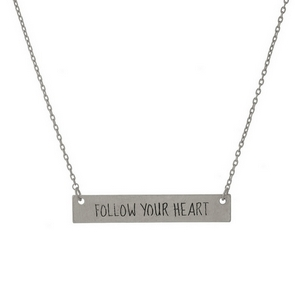 "Dainty silver tone necklace with a bar focal, stamped with ""Follow Your Heart."" Approximately 16"" in length."