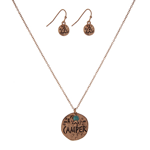"""Gold tone necklace set with a circle pendant stamped with """"Happy Camper"""" and accented with a tipi charm and matching fishhook earrings. Approximately 16"""" in length."""