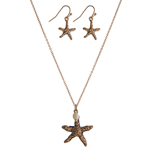 "Gold tone necklace set with a starfish pendant and matching fishhook earrings. Approximately 16"" in length."