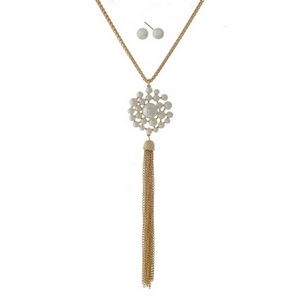 "Gold tone necklace set with a cream pearl flower pendant and a chain tassel. Approximately 32"" in length."