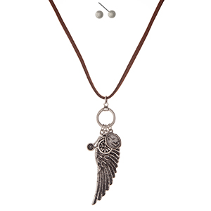 "Brown faux suede cord necklace set with a silver tone wing pendant and matching stud earrings. Approximately 30"" in length."