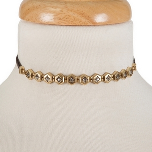 "Black faux leather choker with a gold tone focal and clear rhinestones. Approximately 12"" in length."