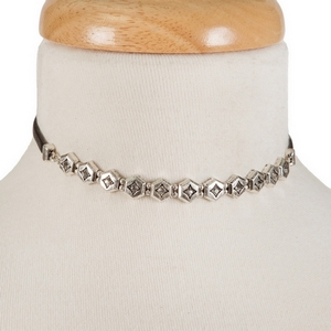 "Black faux leather choker with a silver tone focal and clear rhinestones. Approximately 12"" in length."