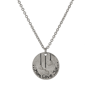 "Dainty silver tone necklace with a circle pendant stamped with ""Mom, Love, Joy."" Approximately 16"" in length."
