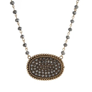 "Gold tone and hematite necklace with a pave pendant. Approximately 32"" in length."
