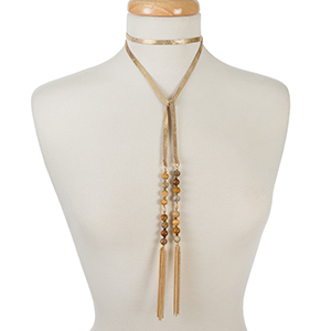"Gold leather wrap necklace with neutral beads and chain tassels. Approximately 52"" in length."