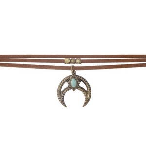 "Brown faux suede choker with a burnished gold tone crescent pendant, accented with a turquoise stone. Approximately 12"" in length."