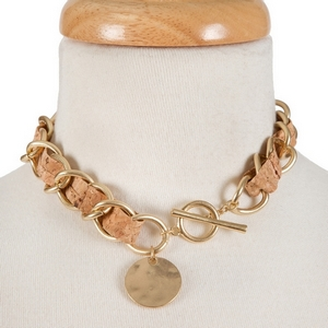 "Gold tone and cork necklace with a toggle closure. Approximately 13"" in length."
