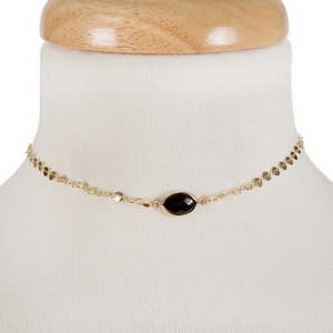 "Dainty gold tone choker with a black stone focal. Approximately 12"" in length."