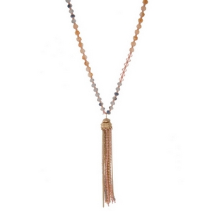 "Pink, peach, and gray beaded necklace with a gold tone chain tassel. Approximately 32"" in length."