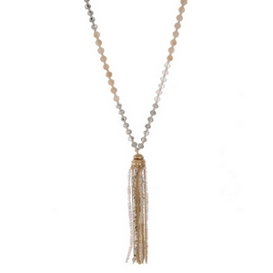 "Ivory, clear, and gray beaded necklace with a gold tone chain tassel. Approximately 32"" in length."