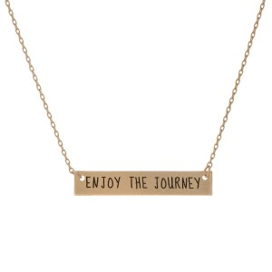 "Matte gold tone bar necklace stamped with ""Enjoy the Journey."" Approximately 14"" in length."