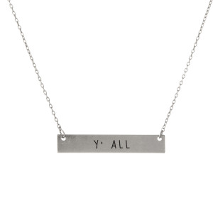 "Matte silver tone bar necklace stamped with ""Y'all."" Approximately 14"" in length."