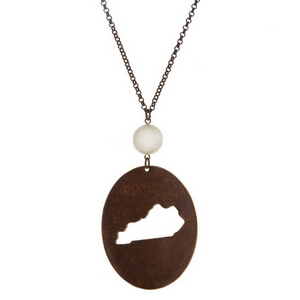 "Burnished copper tone necklace with a Kentucky cutout pendant accented by a pearl bead. Approximately 30"" in length. Oval pendant is approximately 2.5"" tall."