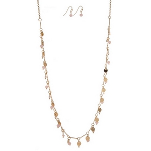 "Dainty gold tone necklace with metal circle and pale pink bead charms, and matching fishhook earrings. Approximately 27"" in length."