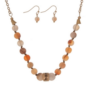 """Matte peach, natural stone beaded necklace with a gold tone bead stamped with """"Thankful"""" and matching fishhook earrings."""