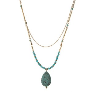 "Gold tone necklace with turquoise faceted beads, featuring a turquoise teardrop stone pendant. Approximately 32"" in length."