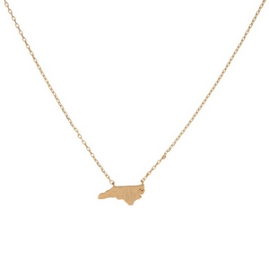 "Dainty gold tone necklace featuring a brushed North Carolina shaped pendant. Pendant approximately 7mm in length. Length adjusts from 16""-18""."