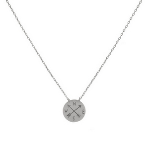 "Dainty silver tone necklace featuring a round brushed pendant with a stamped compass and arrows. Pendant approximately 7mm. Length adjusts from 16""-18""."