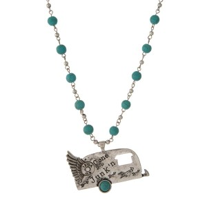 "Silver tone necklace with turquoise beads and a camper pendant, stamped with ""Gone Junkin'."""