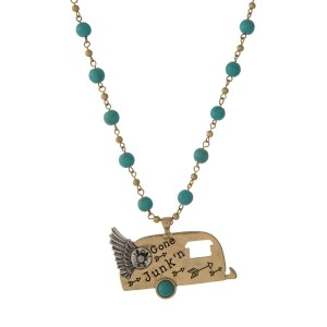 "Gold tone necklace with turquoise beads and a camper pendant, stamped with ""Gone Junkin'."""