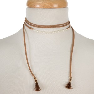 "Brown, faux leather wrap necklace with pearl beads and fabric tassels on the ends. Approximately 60"" in length."