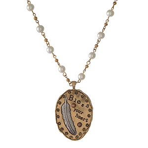 "Gold tone and pearl beaded necklace featuring a gold tone pendant stamped with ""Bless Your Heart."" Approximately 32"" in length."