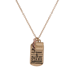 "Dainty gold tone necklace featuring a pendant stamped with ""You are my sun, my moon & all of my stars"" and accented with two small charms. Approximately 16"" in length."
