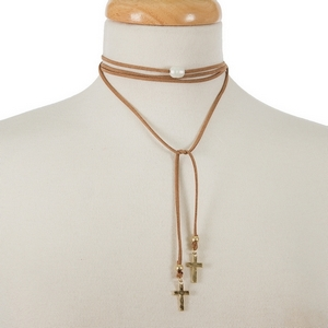 "Tan faux suede wrap necklace with a freshwater pearl bead focal and gold tone crosses on the ends. Approximately 64"" in length."