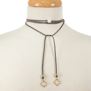 "Gray faux suede wrap necklace with a freshwater pearl bead focal and gold tone clover shapes on the ends. Approximately 64"" in length."