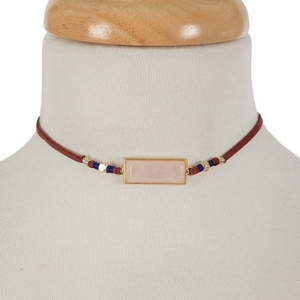 """Red faux suede choker featuring a rose quartz stone focal and gold tone and blue thread accents. Approximately 12"""" in length."""