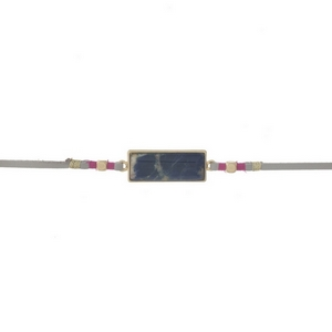 """Gray faux suede choker featuring a sodalite stone focal and gold tone and pink thread accents. Approximately 12"""" in length."""