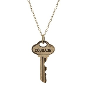 "Burnished gold tone necklace featuring a key pendant, stamped with ""Courage."" Approximately 21"" in length."