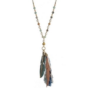 """Burnished gold tone necklace with amazonite natural stone beads, a blue fabric tassel and a cross pendant. Approximately 36"""" in length."""