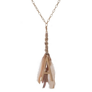"Matte gold tone necklace featuring a pink, peach, and mauve fabric tassel and a block ""A"" initial. Approximately 33"" in length."