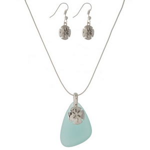 "Silver necklace set featuring a mint green sea glass pendant, a sand dollar charm, and matching fishhook earrings. Approximately 27"" in length."