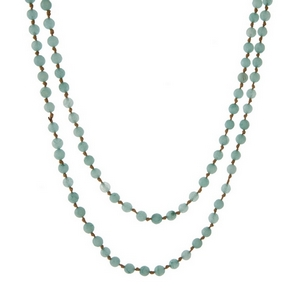 "Tan knotted cord wrap necklace displaying mint green natural stone beads. Approximately 60"" in length."